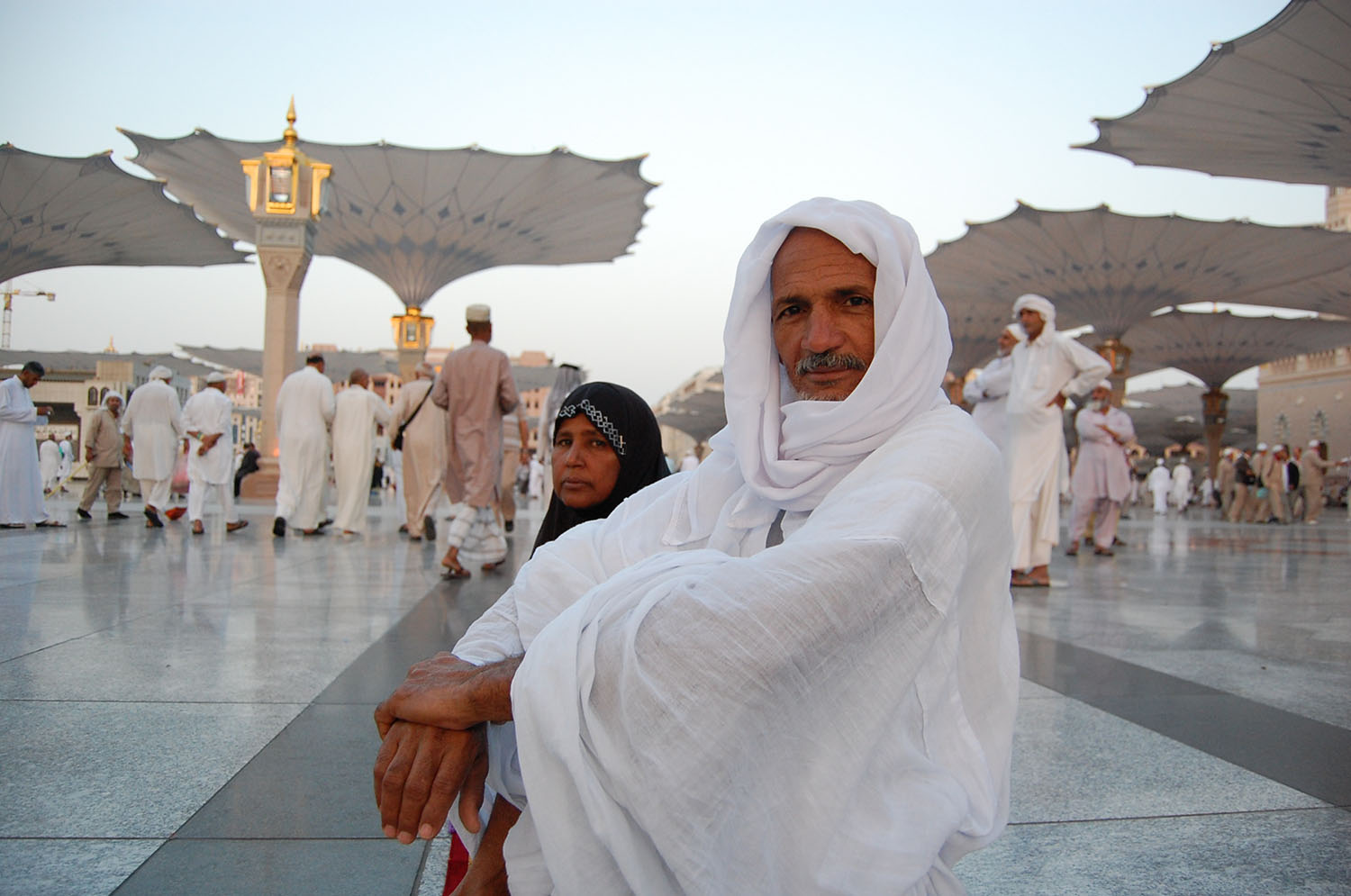 A pilgrim and his wife in the exterior courtyard of the Masjid al-Nabi. Giant retractable umbrellas shield them from the sun.